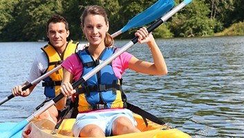 Young woman and man canoeing on a lake